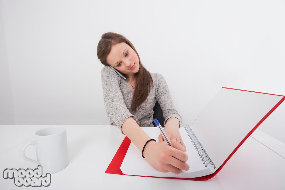 Businesswoman writing notes while answering smart phone in office