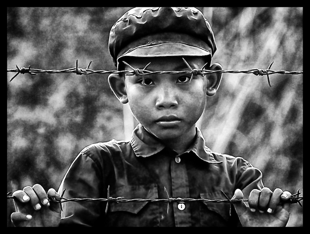 A young Cambodian boy, wearing a Khmer Rouge cap, looks out through barbed wire Sunday, May 3, 1998, at a refugee camp near Huay Samran, Thailand.  Refugees fleeing the fighting between Khmer Rouge and Cambodia forces continue to seek safety in Thailand.