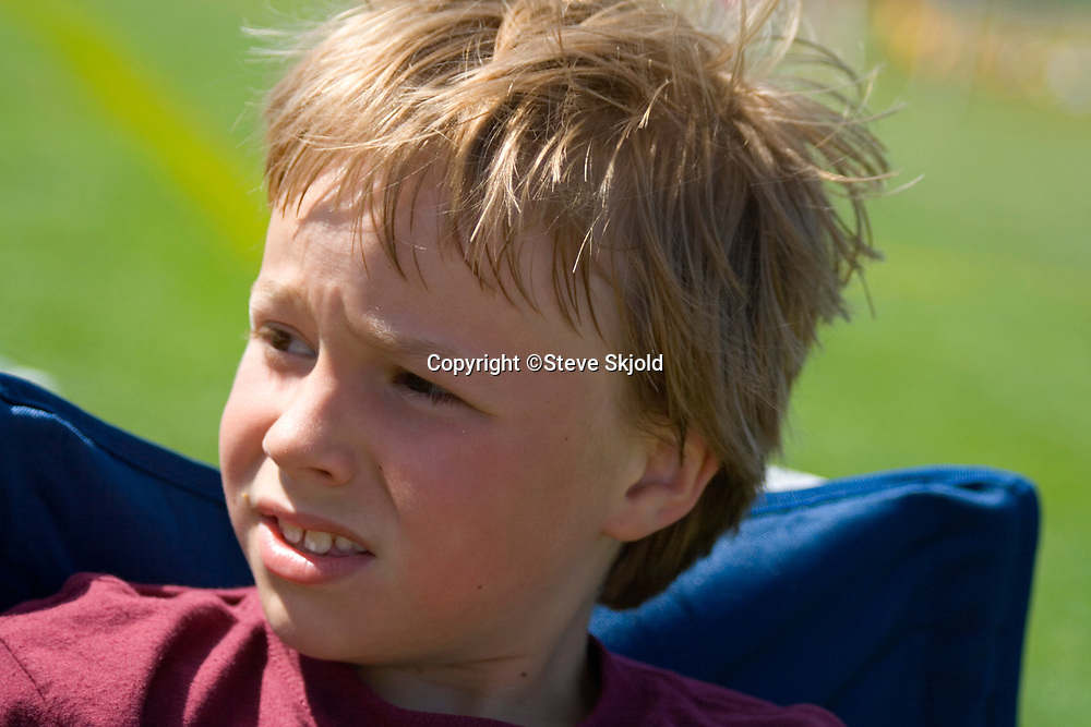 Close-up blond haired boy age 8 sitting in a chair outside. St Paul Minnesota MN USA