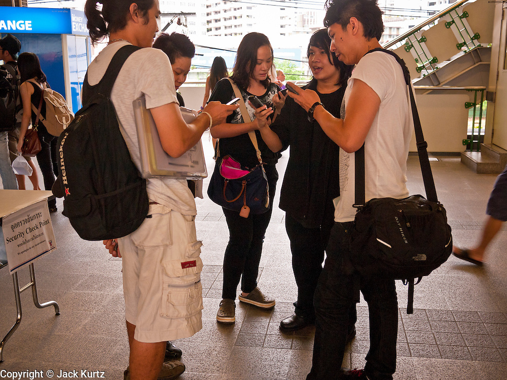 14 JULY 2011 - BANGKOK, THAILAND:   Thai teenagers synch their smart phones in the Nana station on the Sukhumvit line of the BTS Skytrain in Bangkok. The Bangkok Mass Transit System, commonly known as the BTS Skytrain, is an elevated rapid transit system in Bangkok, Thailand. It is operated by Bangkok Mass Transit System Public Company Limited (BTSC) under a concession granted by the Bangkok Metropolitan Administration (BMA). The system consists of twenty-three stations along two lines: the Sukhumvit line running northwards and eastwards, terminating at Mo Chit and On Nut respectively, and the Silom line which plies Silom and Sathon Roads, the Central Business District of Bangkok, terminating at the National Stadium and Wongwian Yai. The lines interchange at Siam Station and have a combined route distance of 55 km.   PHOTO BY JACK KURTZ