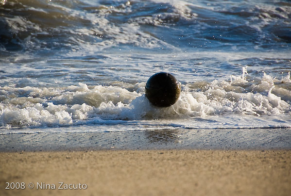 Discarded volleyball bounces along in the waves in the Santa Monica beach.
