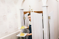 """NAPLES, ITALY - 29 MARCH 2019: A waiter walks out of the kitchen with a dish of garlic and oil spaghetti and with a dish of Carbonara spaghetti at Anonymous Trattoria, a restaurant in Naples, Italy, on March 29th 2019.<br /> <br /> Anonymous Trattoria is a traditional Neapolitan trattori which focuses on some dishes of the Neapolitan culinary tradition that have by now disappeared from the Neapolitan trattorias: from the """"minestra maritata"""" (married soup, a happy marriage of vegetables and meat) to the soup of soffritto (a strong sauce of tomatoes, peppers and meats) to the tripe in the sauce (the recovery of the waste parts of the meat), to the very simple garlic and oil spaghetti."""