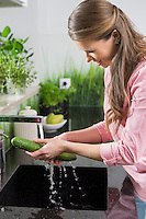 Smiling woman washing cucumber in kitchen