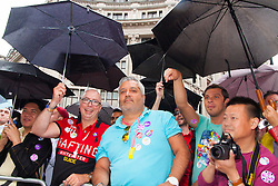 London, June 28th 2014. Spectators shelter from the rain as the Pride London parade proceeds through the city's streets.