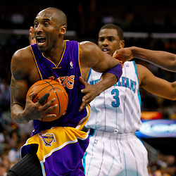 Mar 29, 2010; New Orleans, LA, USA; Los Angeles Lakers guard Kobe Bryant (24) drives past New Orleans Hornets guard Chris Paul (3) and forward James Posey (right) during the second half at the New Orleans Arena. The Hornets defeated the Lakers 108-100. Mandatory Credit: Derick E. Hingle-US PRESSWIRE