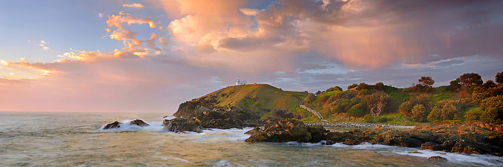 A sectacular sunrise lights up a summer shower above Tacking Point Lighthouse near Port Maquarie, New South Wales, Australia.