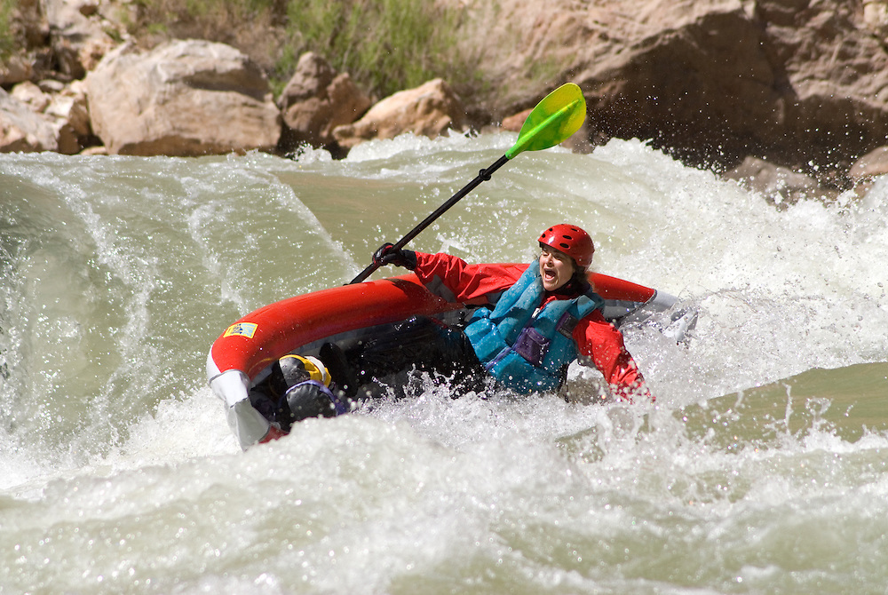 Woman paddling an inflatable kayak that's on it's way towards flipping in a rapid on the Colorado River in the Grand Canyon, Arizona.