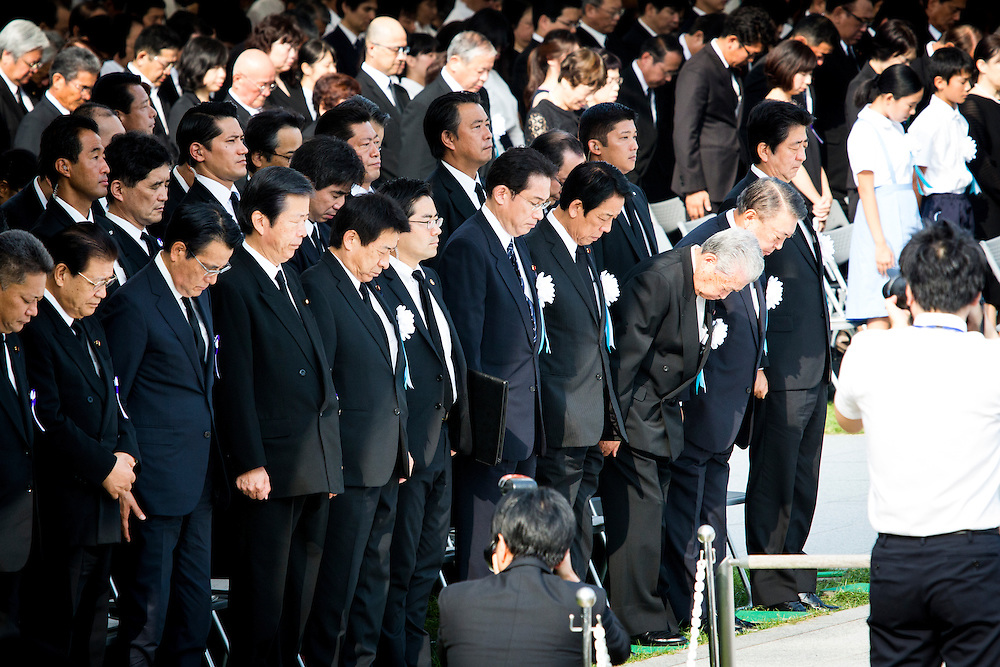 """HIROSHIMA, JAPAN - AUGUST 6 : Japanese Prime Minister Shinzo Abe (right) with other delegates pays respect for a moment of prayer to the atomic bomb victims during the 71st anniversary of the atomic bombing on Hiroshima at Hiroshima Peace Memorial Park in Hiroshima, western Japan, Saturday, August 6, 2016. Japan marked the 71st anniversary of the atomic bombing on Hiroshima. On August 6, 1945, during World War II, the United States dropped a uranium gun-type atomic bomb named """"Little Boy"""" on the city of Hiroshima which instantly killed an estimated 80,000 people, tens of thousands more would later die of radiation exposure. Three days later, a second American B-29 bomber dropped a plutonium implosion-type bomb """"Fat Man"""" on Nagasaki, killing an estimated 40,000 people.  (Photo: Richard Atrero de Guzman/NURPhoto)"""
