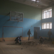 DONETSK, UKRAINE - OCTOBER 19, 2014: Volunteer workers clean the debris from the gymnastic pavilion of School 61 in central Donetsk, hours after it was hit by shellfire claimed to be shot by the Ukrainian National Guard during fighting for the control of the city's airport area. CREDIT: Paulo Nunes dos Santos