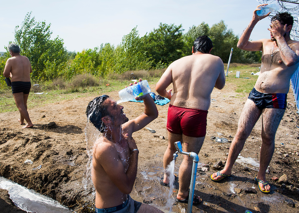 Migrants bathe at a spigot next to the Hungarian border fence on September 17, 2015 in Horgos, Serbia. Thousands of migrants were left in limbo after Hungarian police sealed the border with a barbed wire fence and used tear gas to push back crowds.