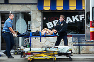 The victim of a stabbing is put onto a gurney Wednesday afternoon outside of Jimmy's Down The Street Restaurant on Sherman Avenue. The stabbing occurred at the Budget Motel under unknown circumstances sometime around 1:40pm. The suspect has not currently been located.
