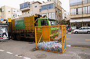 Israel, Tel Aviv, Plastic bottle recycling bin and a garbage collection truck