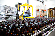 Bottles at the beginning of the assembly line. Ninkasi is a regional craft brewery making beers in the Northwest style. Their location in Eugene, Oregon affords regional access for their primary ingredients, which include: Water, Malt, Hops and Yeast. With the strong regional hop industry, and access to the McKenzie River, source of some of the cleanest water in the world, Ninkasi is well positioned for their goal of brewing high quality craft beers. The beer's namesake, Ninkasi, was the Sumerian goddess of fermentation.