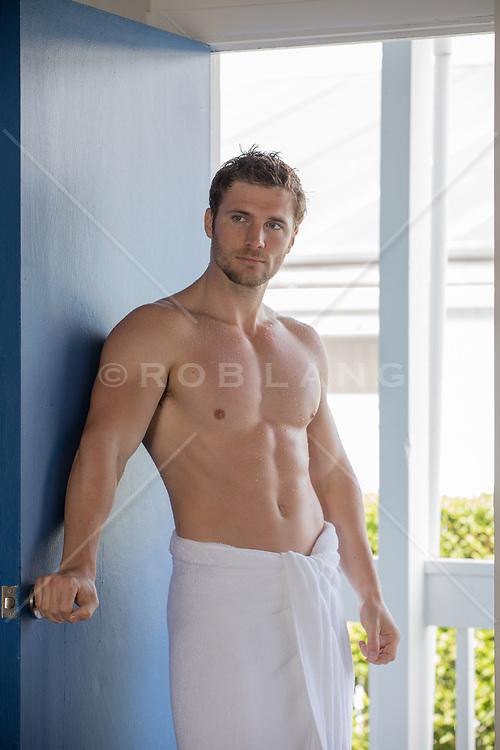 muscular man in a towel by a doorway