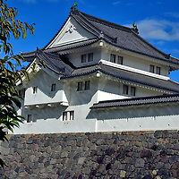 Hitsujisaru Yagura at Sunpu Castle in Shizuoka, Japan<br /> Hitsujisaru Yagura is a reproduction of a wooden gate built at Sunpu Castle in the early 17th century. Its hip and gable roof design is called irimoya-zukuri. Although Higashigomon (East Gate) looks decorative, it was designed for battle. The fa&ccedil;ade includes narrow arrow slits (ya-sama) plus openings for muskets (teppo-sama) and cannons (taiho-sama). Assuming an enemy reached the moat, they were pummeled by falling stones hurdled from roof slats called ishi-sama. No wonder the Japanese named a castle entrance koguchi meaning &ldquo;tiger&rsquo;s mouth.&rdquo;