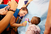 Patient Imaging Technician Brooke Gordon from the USA entertains the patients during the first part of screening at Clinique Ngaliema...Operation Smile South Africa.Clinique Ngaliema, Avenue Des Cliniques.KInshasa, DRC Mission, June 3rd-12th 2011..© Zute & Demelza Lightfoot.www.lightfootphoto.com...