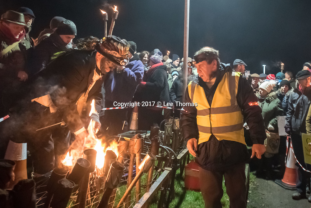 Much Marcle, Herefordshire, UK. 6th January 2018. Pictured:  Torches are lit and distributed to the crowd prior to the  ceremonial march to the orchard. / Hundreds of people both young and old gathered at the Westons Cider Mill and adjoining orchard to take part in the traditional Wassail ceremony. The event at Much Marcle in Herefordshire was attended by the Silurian morris side who entertained the crowd with witty repartee, raucous dancing and music. According to their website, the true origins of blackened faces are lost to history, but are widely believed to be simply a form of disguise, possibly to overcome the oppressive anti-begging laws of the 17th century, and the eternal embarrassment of being a morris man. The orchard-visiting wassail refers to the ancient custom of visiting orchards in cider-producing regions of England, reciting incantations and singing to the trees to promote a good harvest for the coming year.  // Lee Thomas, Tel. 07784142973. Email: leepthomas@gmail.com  www.leept.co.uk (0000635435)