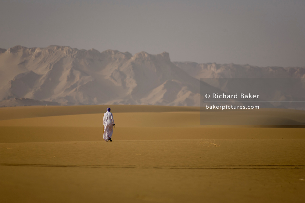 leaving footprints, a Bedouin walks away into desert sand dunes at al-Galamun, near Dahkla Oasis, Western Desert, Egypt. The past few decades have been difficult for traditional Bedouin culture due to changing surroundings and the establishment of new resort towns on the Red Sea coast, such as Sharm el-Sheikh. Bedouins in Egypt are facing a number of challenges: erosion of traditional values, unemployment, and various land issues. The Western Desert covers an area of some 700,000 km2, thereby accounting for around two-thirds of Egypt's total land area. Dakhla Oasis is one of the seven oases of Egypt's Western Desert (part of the Libyan Desert). It lies in the New Valley Governorate, 350 km (220 mi.) and measures approximately 80 km (50 mi) from east to west and 25 km (16 mi) from north to south.