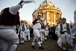 © London News Pictures. 01/05/2016. Oxford, UK. Morris Dancers perform in front of Radcliffe Camera at Oxford University as part of May Day celebrations in the early hours of the morning. This year people were again prevented from jumping from Magdalen bridge in to the water due to serious injuries sustained at a previous years event . Photo credit: Ben Cawthra/LNP