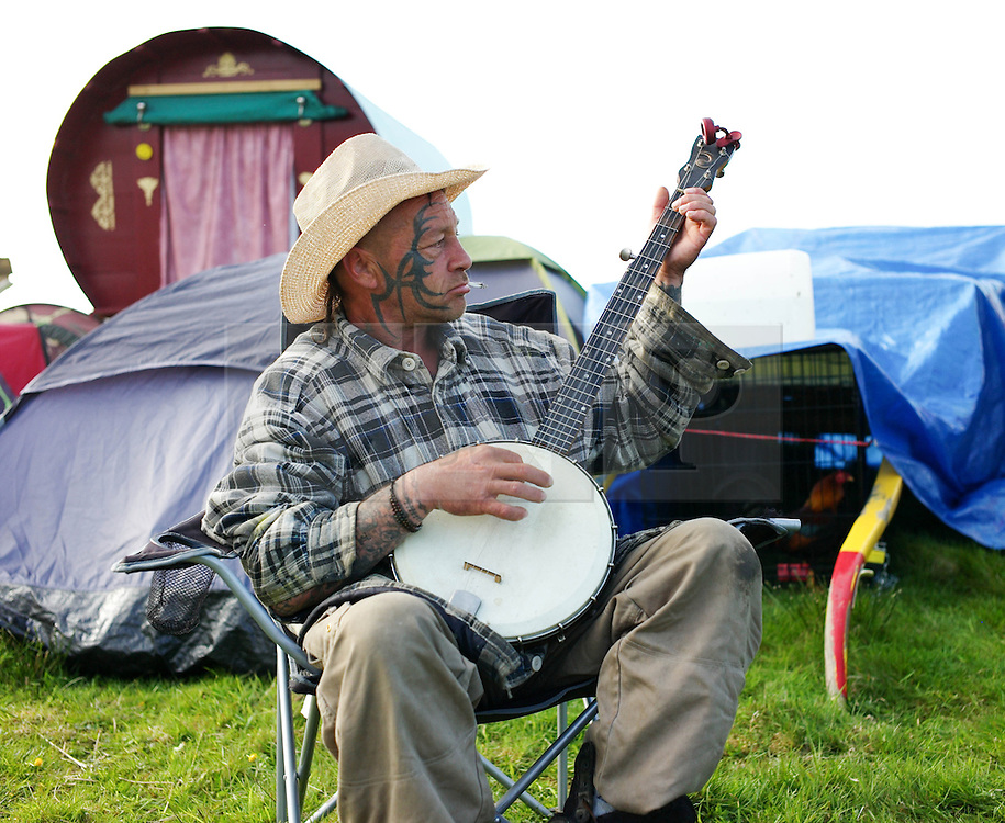 © Licensed to London News Pictures. 06/06/2013<br /> <br /> Appleby, Cumbria, United Kingdom.<br /> <br /> A traveller called 'Slick' from Burnley plays his banjo during the annual gathering of gypsies and travellers as it takes place on 6 June, 2013 in Appleby, Cumbria. The event remains one of the largest and oldest events in Europe and gives the opportunity for travelling communities to meet friends, celebrate their music, their folklore and to buy and sell horses.<br /> <br /> The five day event has existed under the protection of a charter granted by King James II in 1685 and it remains the most important event in the gypsy and traveller calendar.<br /> <br /> Photo credit : Ian Forsyth/LNP