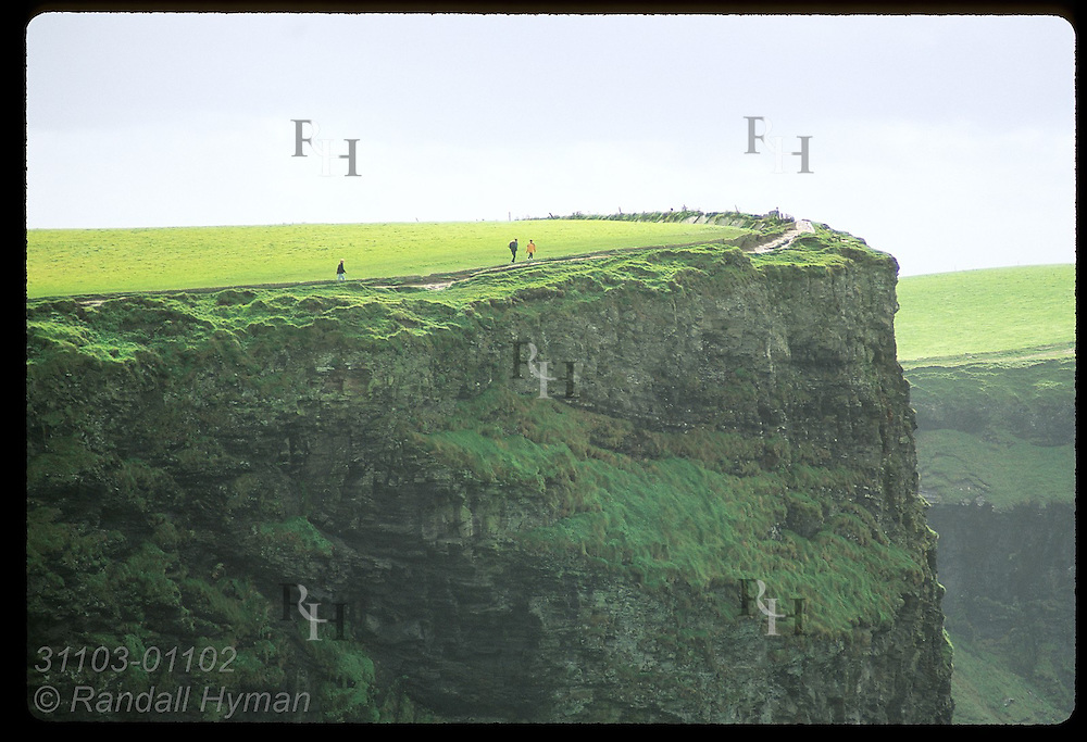 Distant visitors walk along edge of Cliffs of Moher on a September afternoon; Ireland.