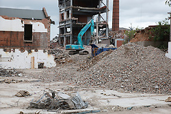 Demolition of factory showing digger, rubble etc.