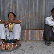 A young coconut vendor and a man in a typical Indian sitting position, outside a cinema hall in Delhi. May 2007
