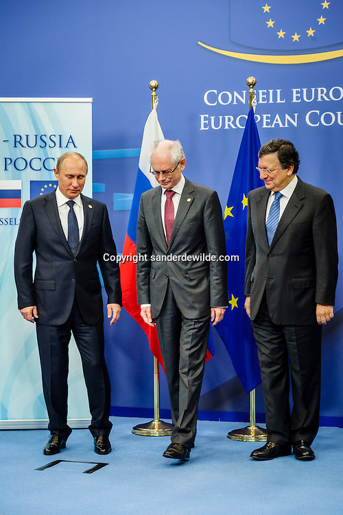 Russian President Vladimir Putin is welcomed by European Council President Herman Van Rompuy (R) ahead of an European Union-Russia summit in Brussels December 21, 2012. from left to right:  Vladimir Putin,President of Russia,  Herman van Rompuy, President of the European Council, an J.M. Barroso, President of the European Commission  pose for a group picture while Herman Van Rompuy starts to walk away