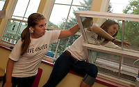 Laconia High School students Erin Cashman and Mary Santos clean windows at Lakes Region Child Care Services Friday morning during United Way's annual Day of Caring event.  (Karen Bobotas/for the Laconia Daily Sun)