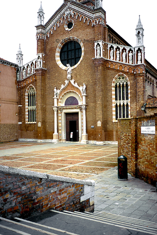 Venetian Gothic church of Madonna dell'Orto, Cannaregio district, Venice; facade and campo from bridge.  Built early 15th c, restored about 1970.  The little campo is deserted, though the church door is open, with a sign on an easel giving service information.