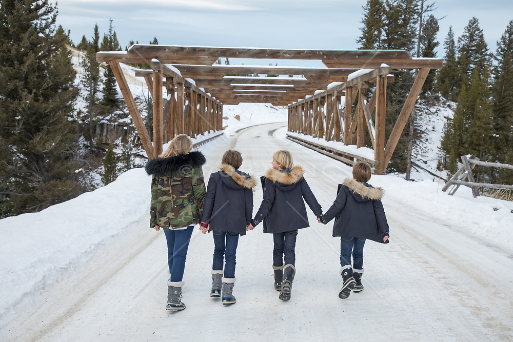 Winter scene of four children walking on a snowy road towards a bridge