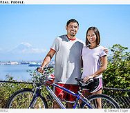 Young couple with bike with Mount Rainier and Puget Sound in the background.
