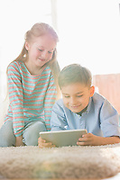Siblings using digital tablet on floor at home
