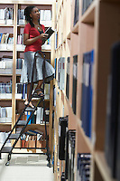 Office worker standing on ladder in file storage room selective focus side view