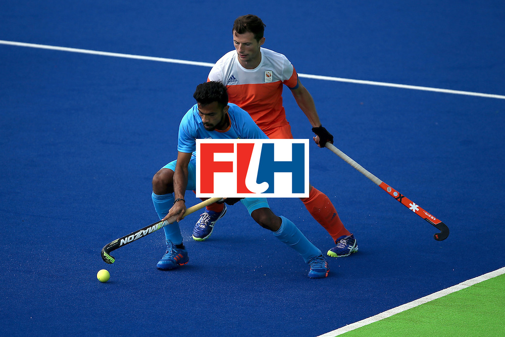 RIO DE JANEIRO, BRAZIL - AUGUST 11:   Sander Baart #13 of Netherlands defends against Chandanda Thimmaiah #32 of India during a Men's Preliminary Pool B match on Day 6 of the Rio 2016 Olympics at the Olympic Hockey Centre on August 11, 2016 in Rio de Janeiro, Brazil.  (Photo by Sean M. Haffey/Getty Images)