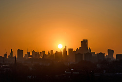 © Licensed to London News Pictures. 11/02/2020. London, UK. The sun rises from behind the City of London, seen from Primrose hill in North London. Large parts of the UK are recovering from the affects of storm Ciara which caused heavy flooding and damage from high winds. Photo credit: Ben Cawthra/LNP