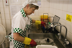 Dinner lady washing up dishes after school lunch,