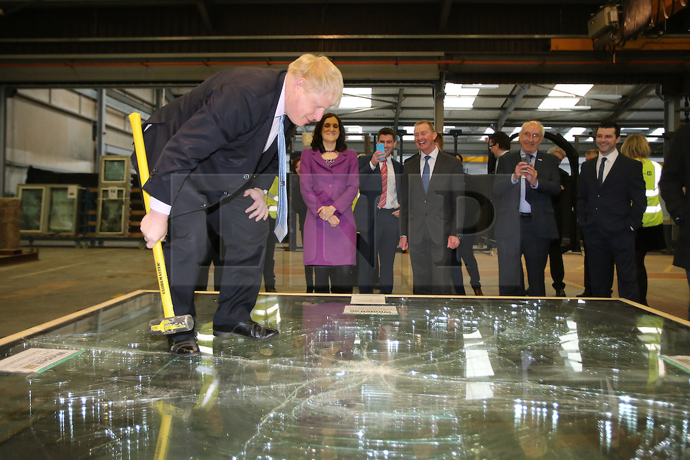 © Licensed to London News Pictures. 29/02/2016. Magherafelt, Northern Ireland, Mayor of London, Boris Johnson MP,tests a safety glass with a hammer during a tour of Windell factory in Magherafelt,  Northern Ireland. Boris was visiting businesses that are supported by investment from Transport for London. Photo credit : Paul McErlane/LNP