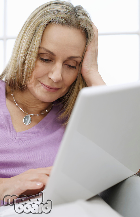 Mid-adult woman using laptop