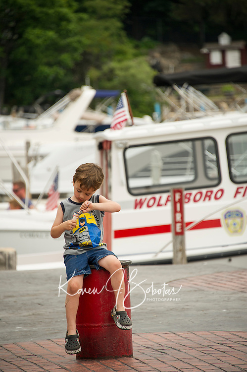 Young lad enjoying an ice cream cone at the docks on a Summer's day in Wolfboro, NH.  ©2015 Karen Bobotas Photographer