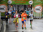 Roomy Kashlan, 11, of Alpharetta, Ga., leads a pack of runners across the Luckie 5K finish line during a steady rain on Sunday, March 22, 2015, in Atlanta. David Tulis / AJC Special