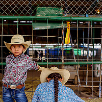 Kyler Kee leans on a fence while his brother Ryan Kee helps repair a spur on his boot during the wooly riding contest at the Navajo Nation Fair in Window Rock Friday.