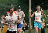 Runners get cooled off the the spray from a spectator's hose during the 25th annual Orange Classic 10K road race in Middletown, N.Y., on June 11, 2005. The weather for the race was hot and humid.