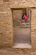 A baby girl walks through an ancient doorway at Pueblo Bonito. Pueblo Bonito is a monumental public building (Puebloan Great House) occupied from around 828 to 1126 AD, now preserved at Chaco Culture National Historical Park, New Mexico, USA. The huge D-shaped complex of Pueblo Bonito enclosed two plazas with dozens of ceremonial kivas, plus 600 rooms towering 4 and 5 stories above the valley floor. The functions of this building included ceremony, administration, trading, storage, hospitality, communications, astronomy, and burial, but few living quarters. Chaco Culture NHP hosts the densest and most exceptional concentration of pueblos in the American Southwest and is a UNESCO World Heritage Site, located in remote northwestern New Mexico, between Albuquerque and Farmington. From 850 AD to 1250 AD, Chaco Canyon advanced then declined as a major center of culture for the Ancient Pueblo Peoples. Chacoans quarried sandstone blocks and hauled timber from great distances, assembling fifteen major complexes that remained the largest buildings in North America until the 1800s. Climate change may have led to its abandonment, beginning with a 50-year drought starting in 1130.
