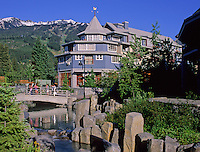The Village Park bridge crosses a stream in Whistler Village, summer.