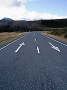 Many New Zealand roads have painted arrows on them to remind the numerous tourists to drive on the left side of the road. Near Te Anau, entering Fiordland National Park, New Zealand