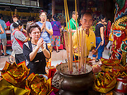"07 AUGUST 2014 - BANGKOK, THAILAND:       People pray at an alter at Pek Leng Keng Mangkorn Khiew Shrine. Thousands of people lined up for food distribution at the Pek Leng Keng Mangkorn Khiew Shrine in the Khlong Toei section of Bangkok Thursday. Khlong Toei is one of the poorest sections of Bangkok. The seventh month of the Chinese Lunar calendar is called ""Ghost Month"" during which ghosts and spirits, including those of the deceased ancestors, come out from the lower realm. It is common for Chinese people to make merit during the month by burning ""hell money"" and presenting food to the ghosts. At Chinese temples in Thailand, it is also customary to give food to the poorer people in the community.    PHOTO BY JACK KURTZ"