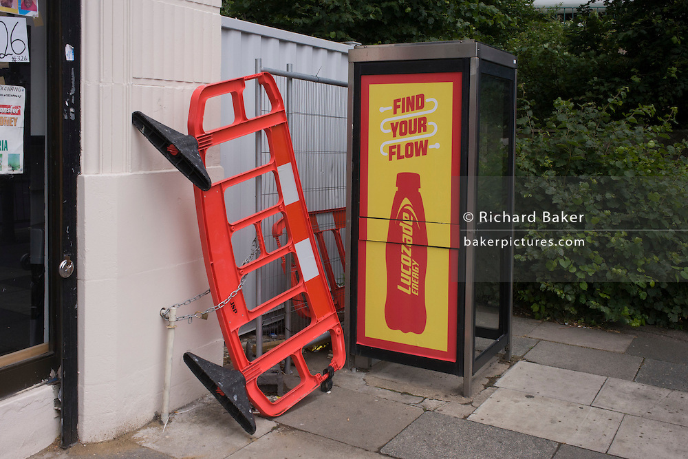 Upright road barrier and Lucozade advert in south London.