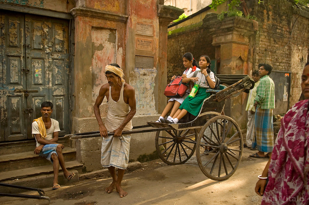 Kolkata's (Calcutta) rickshaw pullers take children to school and people to work around Ripon Street in central Calcutta, September 18, 2007. This congested city was the first city of the colonial British and  now it is the only city of India where hand pulled rickshaws are still being pulled. In 1996, the Government of West Bengal announced that it was intending to ban the rickshaws to relieve traffic congestion  but it never was fully enforced. In 2007, the government again pushed to have the ban enforced and a case is currently being decided in the Supreme court that will determine the outcome for the hand pulled rickshaws.