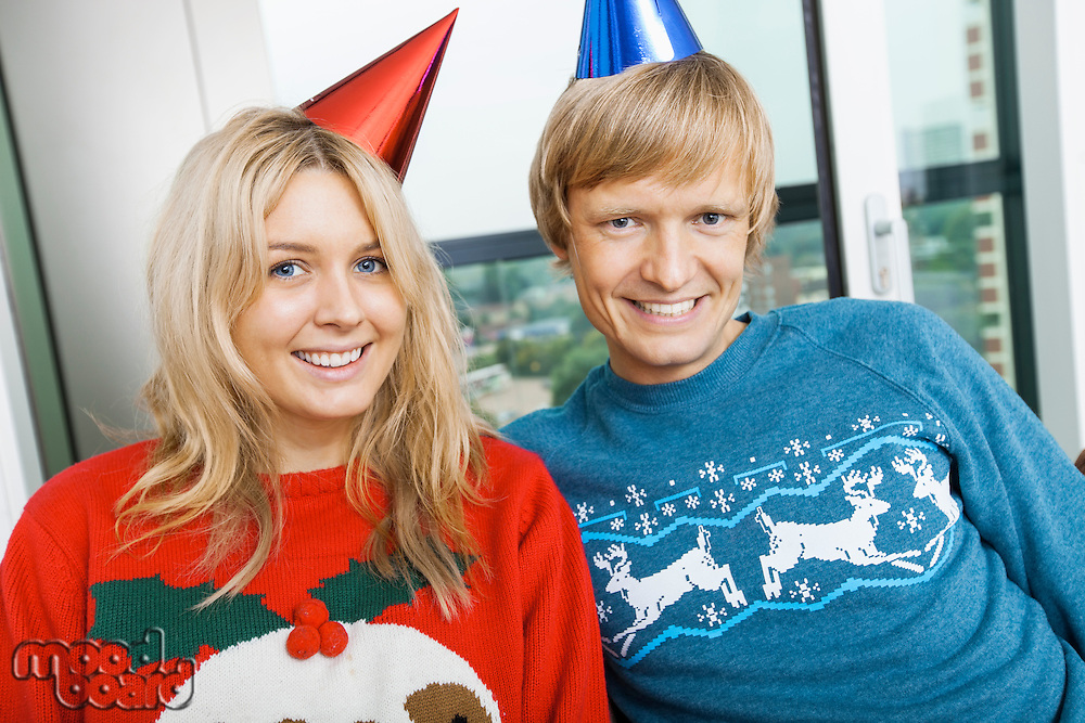 Portrait of smiling couple wearing Christmas sweaters and party hats in living room at home